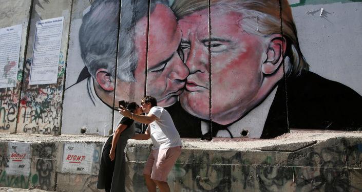 Turyści całujący się na tle graffit przedstawiającego pocałunek Trumpa i Netanjahu