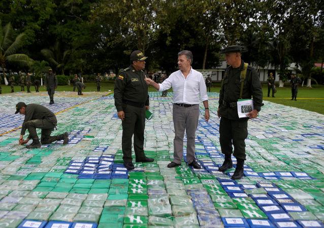 Prezydent Kolumbii Juan Manuel Santon na improwizowanym polu z cegiełek z kokainą w otoczeniu funkcjonariuszy służb specjalnych