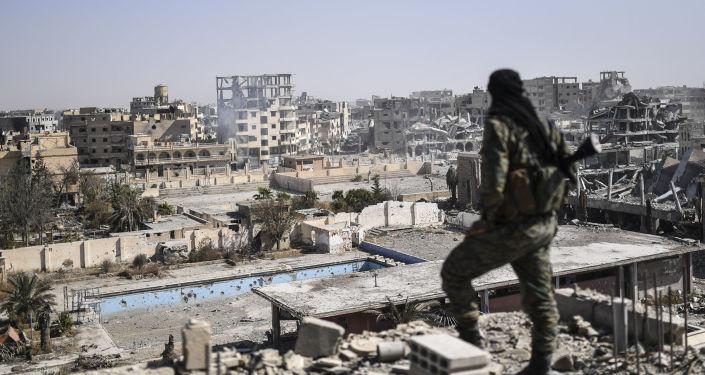Żołnierz Syryjskich Sił Demokratycznych patrzy na Rakkę po jej wyzwoleniu z rąk PI