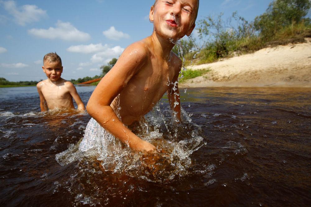Dzieci kąpią się w rzece Stwiha w letni dzień niedaleko wsi Pohost.