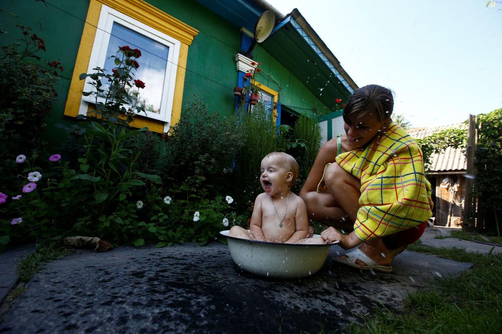 Wnuczka Jekateriny Panczenia Jekaterina kąpie córkę Daszę w letni gorący dzień we wsi Pohost.