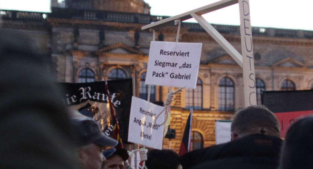 """Protestujący niosą atrapę szubienicy z napisem """"Zarezerwowane dla Angeli Merkel"""" w Dreźnie, Niemcy"""