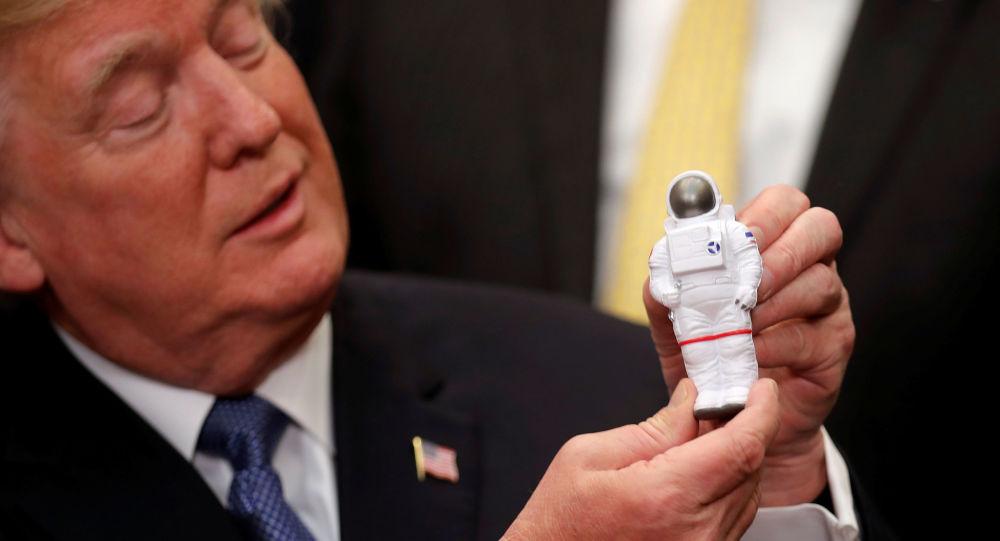Prezydent USA Donald Trump trzymający w rękach figurkę kosmonauty w Waszyngtonie