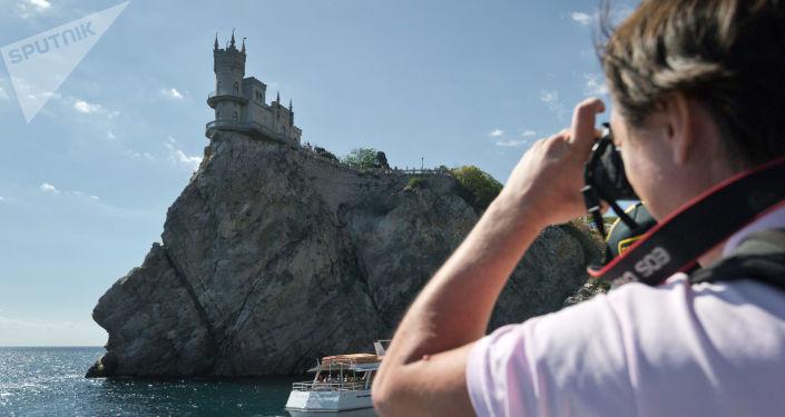 Turysta fotografujący zamek Jaskółcze gniazdo z pokładu motorowca