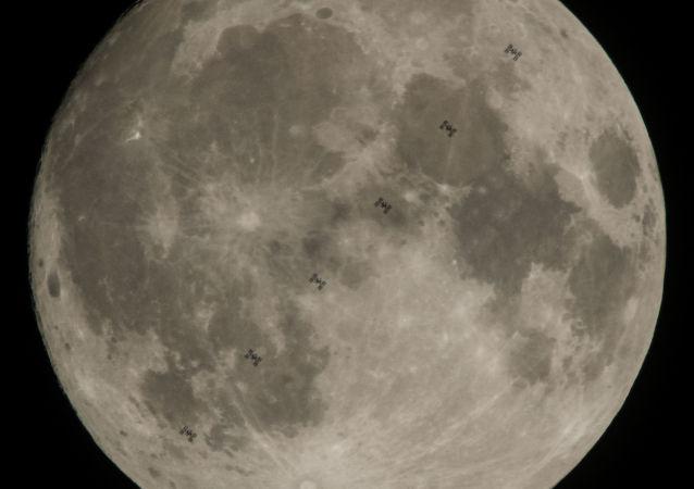 Międzynarodowa Stacja Kosmiczna z szęściosobową załogą na pokładzie na tle Księżyca
