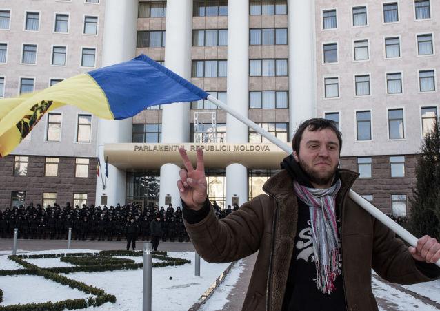 Uczestnik akcji protestacyjnej w Kiszyniowie pod budynkiem Parlamentu Republiki Mołdawii