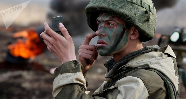 Żołnierz piechoty morskiej nanosi na twarz barwy wojenne przez rozpoczęciem ćwiczeń piechoty morskiej Floty Oceanu Spokojnego w Kraju Nadmorskim