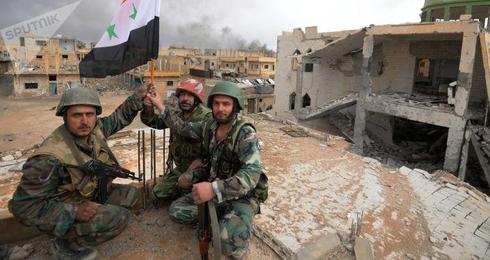 Żołnierze z flagą Syrii w Palmyrze