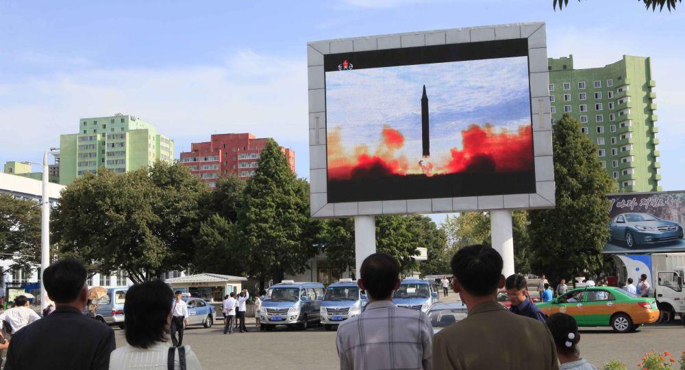 Przechodnie w Pjongjangu oglądają wiadomości o wystrzeleniu rakiety balistycznej Hwasong-12