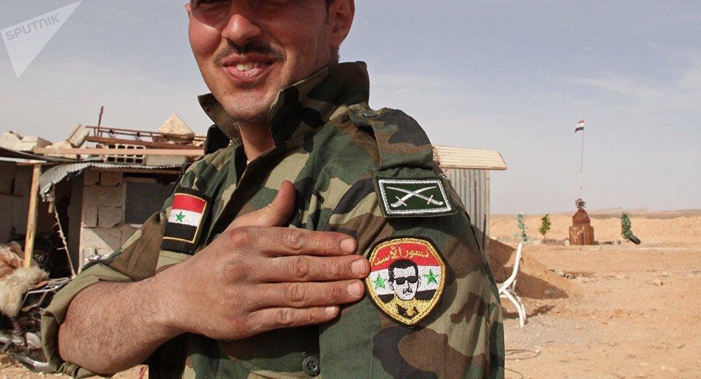 Żołnierz Syryjskiej armii demonstruje naszywkę z portretem Baszara Asada na syryjsko-libańskiej granicy