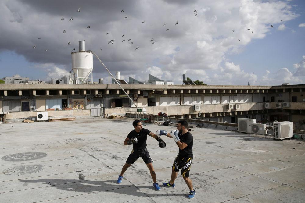 Instruktorzy Doron Turgeman i Michael Alimelech trenują na dachu budynku w mieście Giwatajim.
