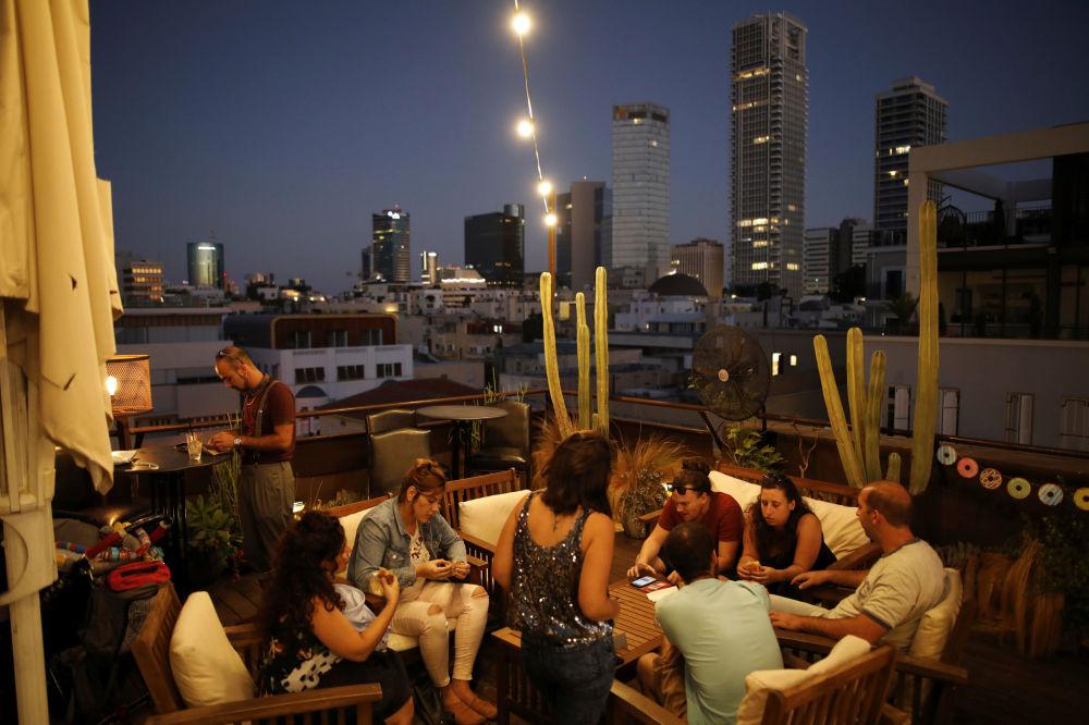Ludzie w barze na dachu hotelu Brown w Tel Awiwie.