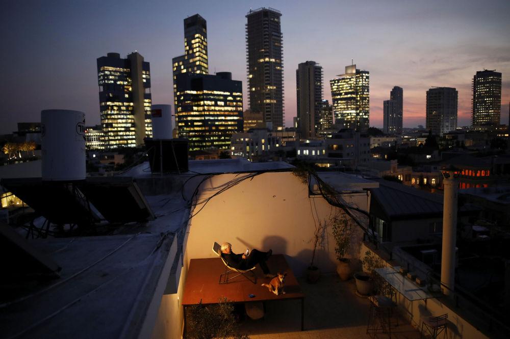 Alexander Flaschenberg siedzi na fotelu na dachu swojego domu w Tel Awiwie.