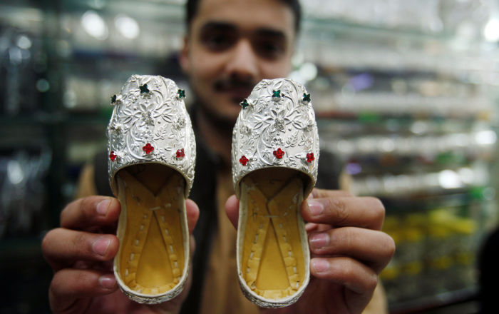 Sprzedawca pokazuje srebrne pantofelki w sklepie jubilerskim na bazarze w Peszewarze, Pakistan.