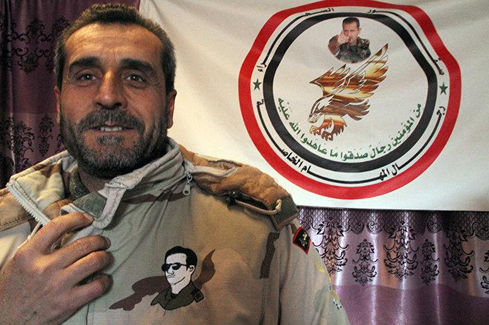 Członek Desert Hawks demonstruje naszywkę z portretem prezydenta Syrii Baszara Asada