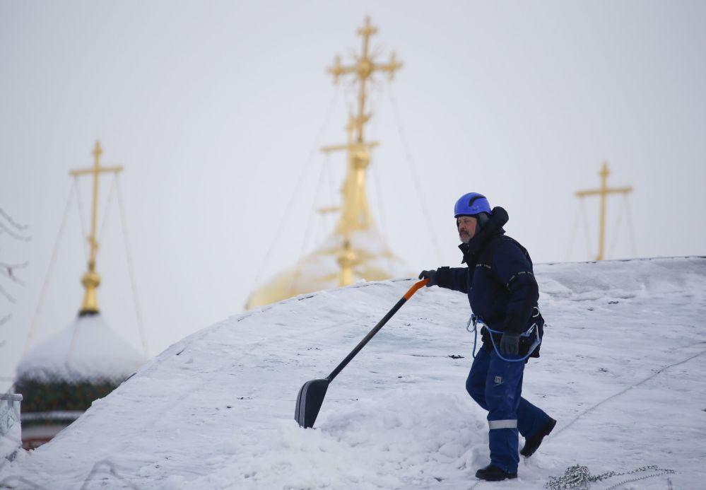 Robotnik oczyszcza dach budynku ze śniegu w centrum Moskwy