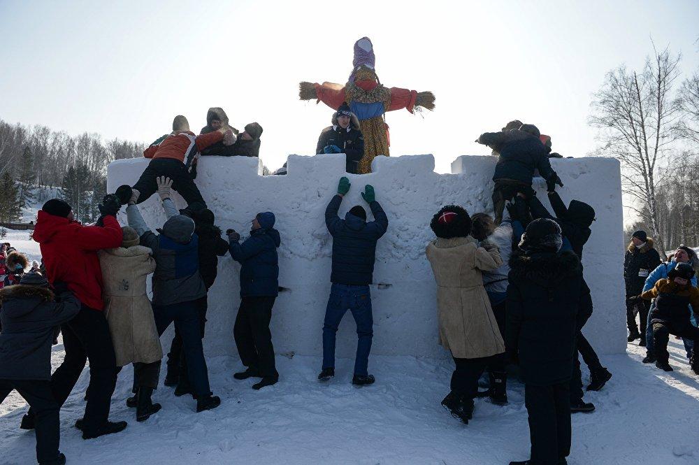 Szturm na śnieżną fortecę podczas świątecznych uroczystości w parku miasta Kolcowo w obwodzie nowosybirskim.