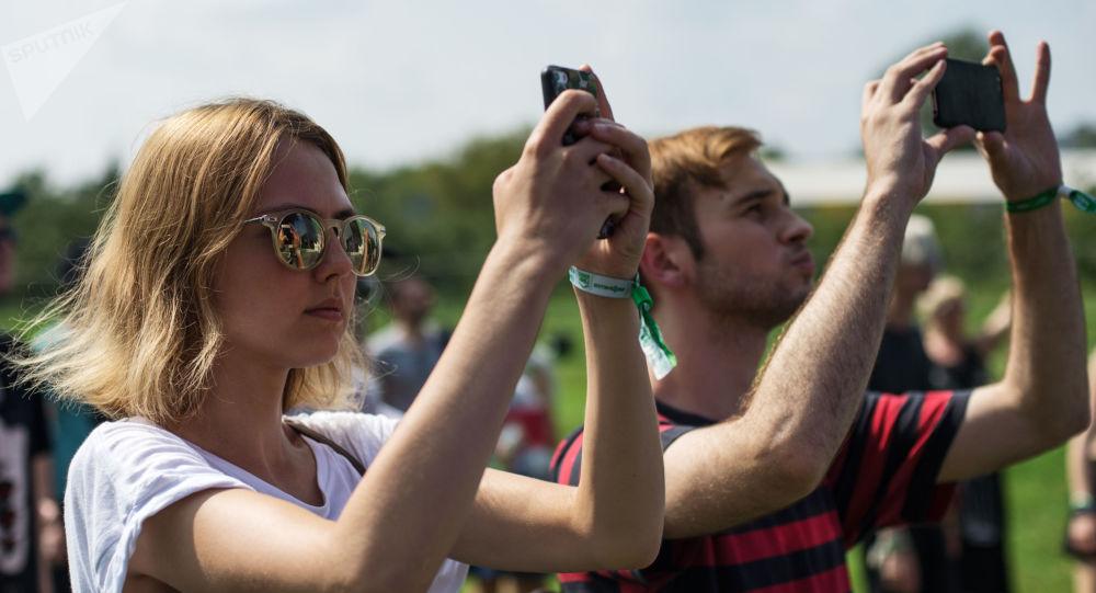 Uczestnicy festiwalu Piknik. Afiszy w Moskwie z telefonami