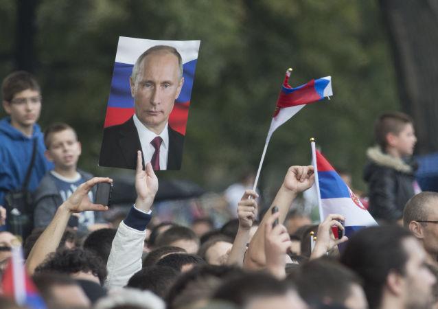 Mieszkańcy Belgradu z portretami prezydenta Rosji Władimira Putina
