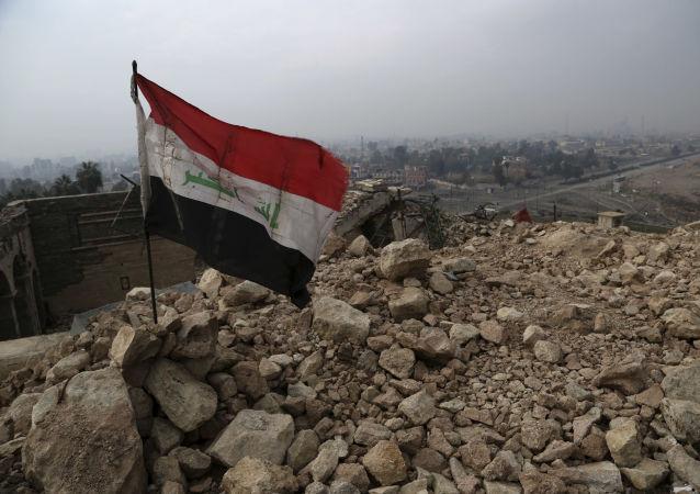 Iracka flaga na ruinach zburzonego meczetu w Mosulu