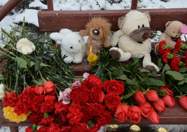 Kwiaty i znicze obok budynku centrum handlowego w Kemerowo