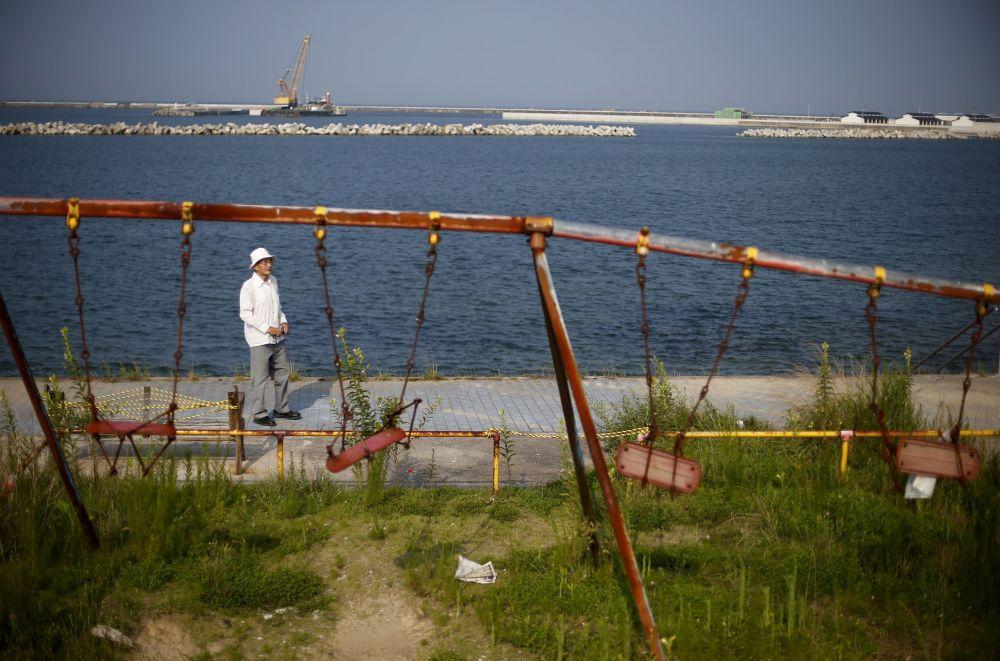 86-letni mieszkaniec prowincji Fukushima Yoshiteru Kohata, który przeżył atak atomowy na Nagasaki, spaceruje nad morzem niedaleko uszkodzonego placu zabaw