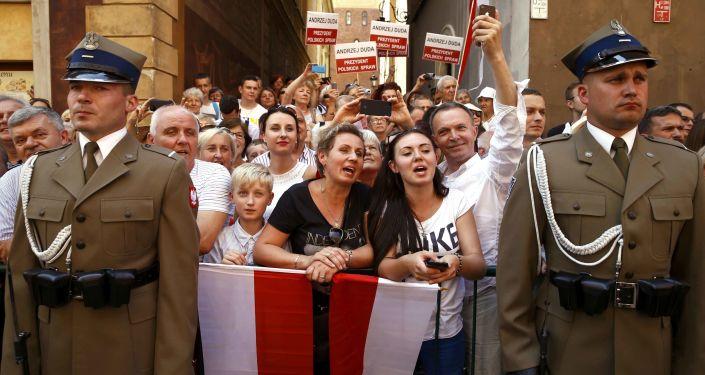 Ludzie witają nowego prezydenta Polski Andrzeja Dudy i jego żonę Agatę Kornhauser-Dudę na ulicach Starego Miasta w Warszawie