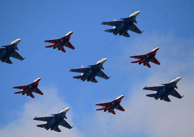 """Wielozadaniowe myśliwce Su-30SM grupy pilotażowej """"Russkije Witjazi i MiG-29 grupy """"Striżi podczas próby generalnej Defilady Zwycięstwa na poligonie wojskowym """"Alabino w obwodzie Moskiewskim"""