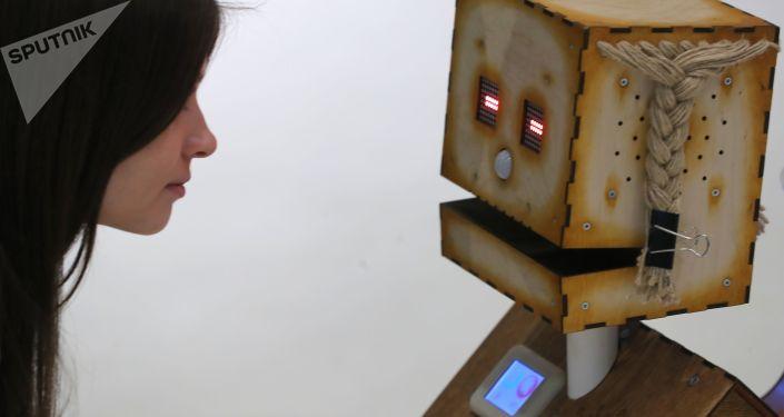 """Gość wystawy ogląda robota """"Derewiankę"""" firmy """"Robodem"""" na  forum """"SKOLKOVO ROBOTICS"""" w Moskwie"""