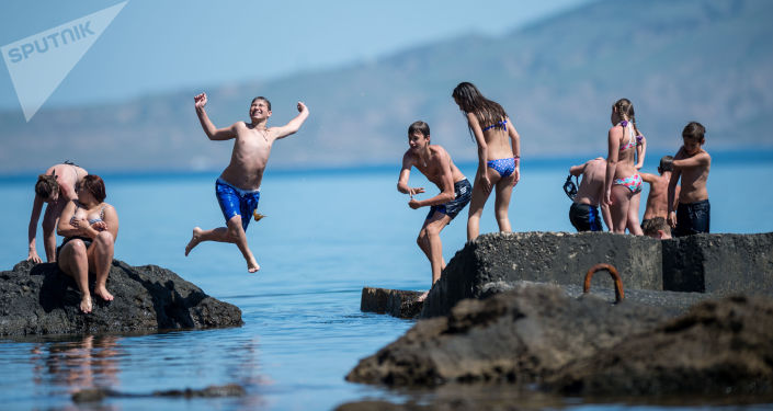 Urlopowicze skaczą do wody z falochronów. Nowy Świat, Krym