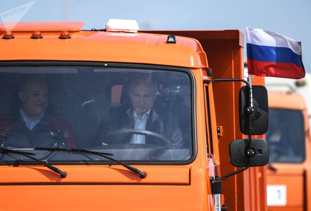 """Prezydent Władimir Putin za kierownicą ciężarówki """"Kamaz"""" podczas przejazdu kolumny sprzętu budowlanego na odcinku drogowym Mostu Krymskiego podczas ceremonii otwarcia przejścia transportowego"""