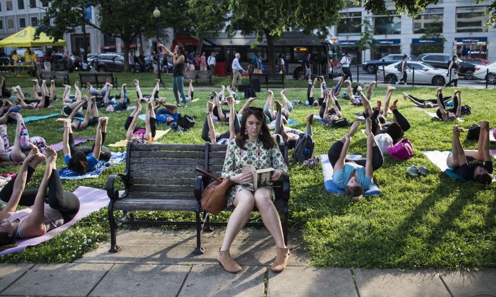 Kobieta czyta książkę podczas sesji grupowej jogi w Waszyngtonie, USA