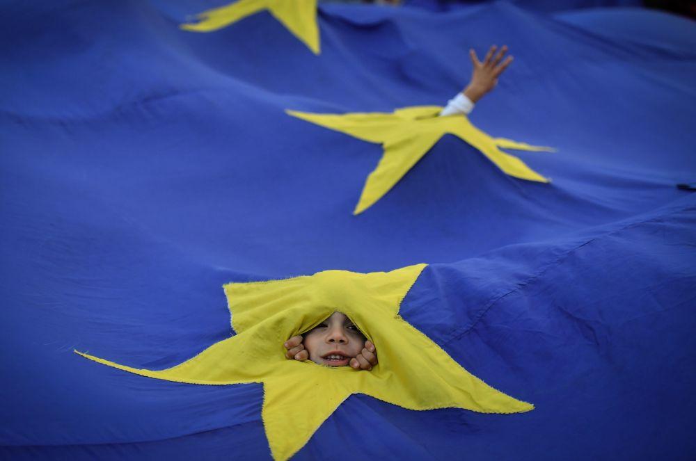 Chłopiec wygląda zza flagi Unii Europejskiej podczas wiecu w Bukareszcie