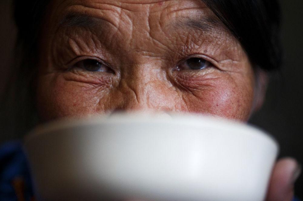 Koczownik Żargal Gombirowannyje pije herbatę z mlekiem w swoim namiocie w lesie niedaleko wsi Cagaannuur, Huvsgel, Mongolia