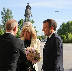 Władimir Putin wręcza bukiet kwiatów żonie Emmanuela Macrona Briggite Macron