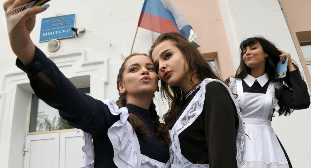 Absolwenci robią sobie selfie przy wejściu do szkoły numer 47 podczas święta zakończenia roku szkolnego w mieście Czita