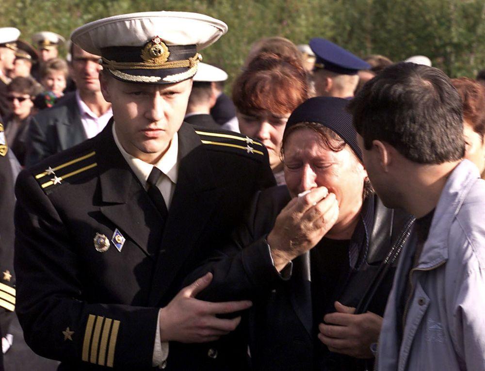 Rosyjski marynarz pomaga kobiecie podczas ceremonii żałobnej
