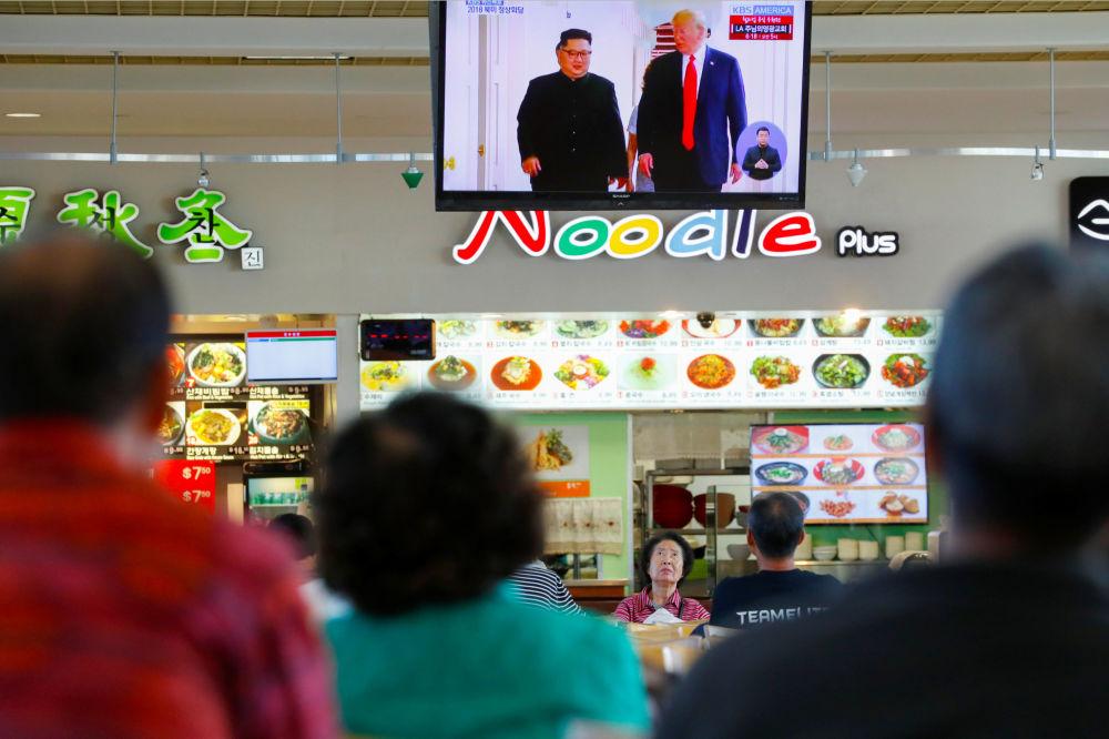 Ludzie oglądają relację ze spotkania Donalda Trumpa i Kim Dzong Una