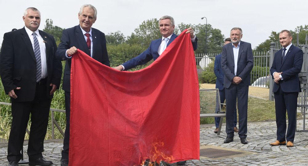 Prezydent Republiki Czeskiej Milos Zeman i szef biura prezydenckiego Vratislav Minar trzymają czerwone płótno podczas rytualnego palenia na Zamku Praskim