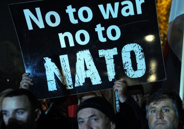Protestujący trzymające plakat z napisem Nie wojnie, nie NATO w Podgoricy