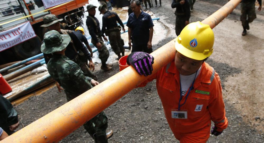 Ratownicy z rurą podczas akcji ratowniczej w pobliżu jaskini w Tajlandii