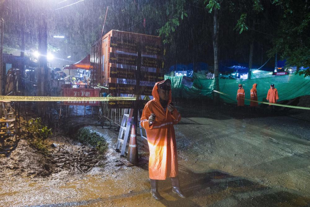 Policja wokół otoczonej strefy przy zalanej jaskini Tham Luang w Tajlandii
