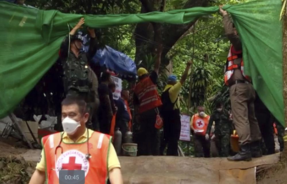 Ratownicy niosą nosze prawdopodobnie z uratowanym chłopcem z zalanej jaskini Tham Luang w Tajlandii