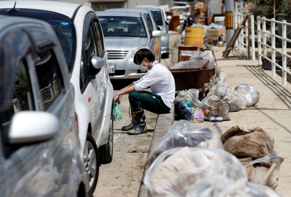 Sprzątanie śmieci w zniszczonym przez powódź mieście Mabi, prefektura Okayama