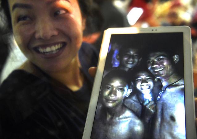 Mama jednego z 12 chłopców zaginionych w jaskini Tham Luang pokazuje zdjęcie swojego syna i trenera jego drużyny piłkarskiej Ekkapola Chantawonga