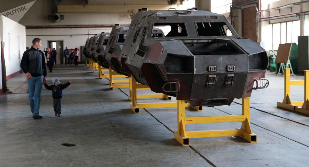"""Odwiedzający cech produkcji transportera opancerzonego """"Dozor B"""" podczas demonstracji sprzętu wojskowego we Lwowskiej Fabryce Pancernej"""