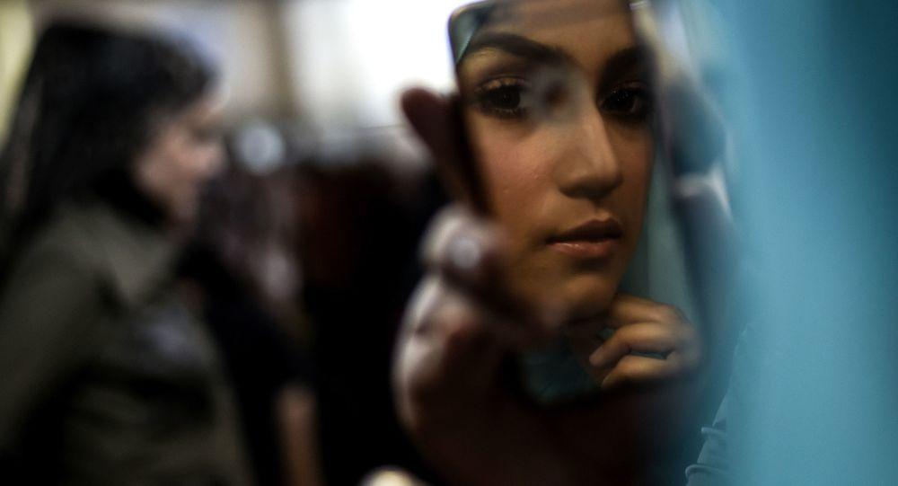 Modelka sprawdza makijaż przed wyjściem na wybieg podczas Tygodnia Mody Islamskiej w Kuala Lumpurze