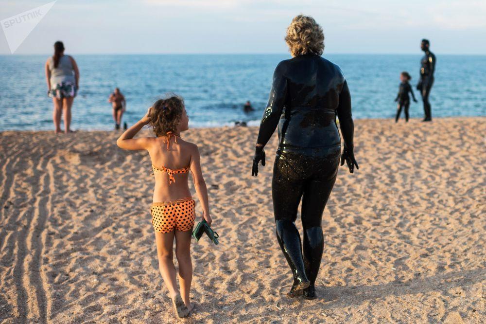 Kąpiele błotne na Krymie (Jezioro Czokrak), kobieta idzie wykąpać się w morzu