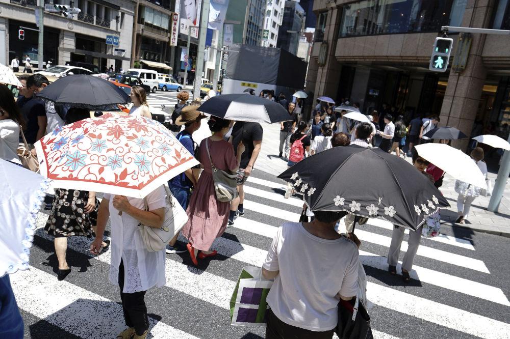 Ludzie chowali się pod parasolami w czasie anomalnych upałów w Tokio
