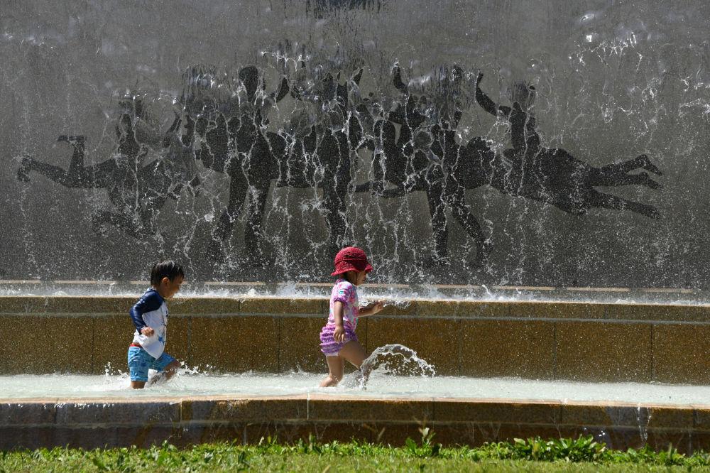 Dzieci bawią się w fontannie podczas anomalnych upałów w Tokio